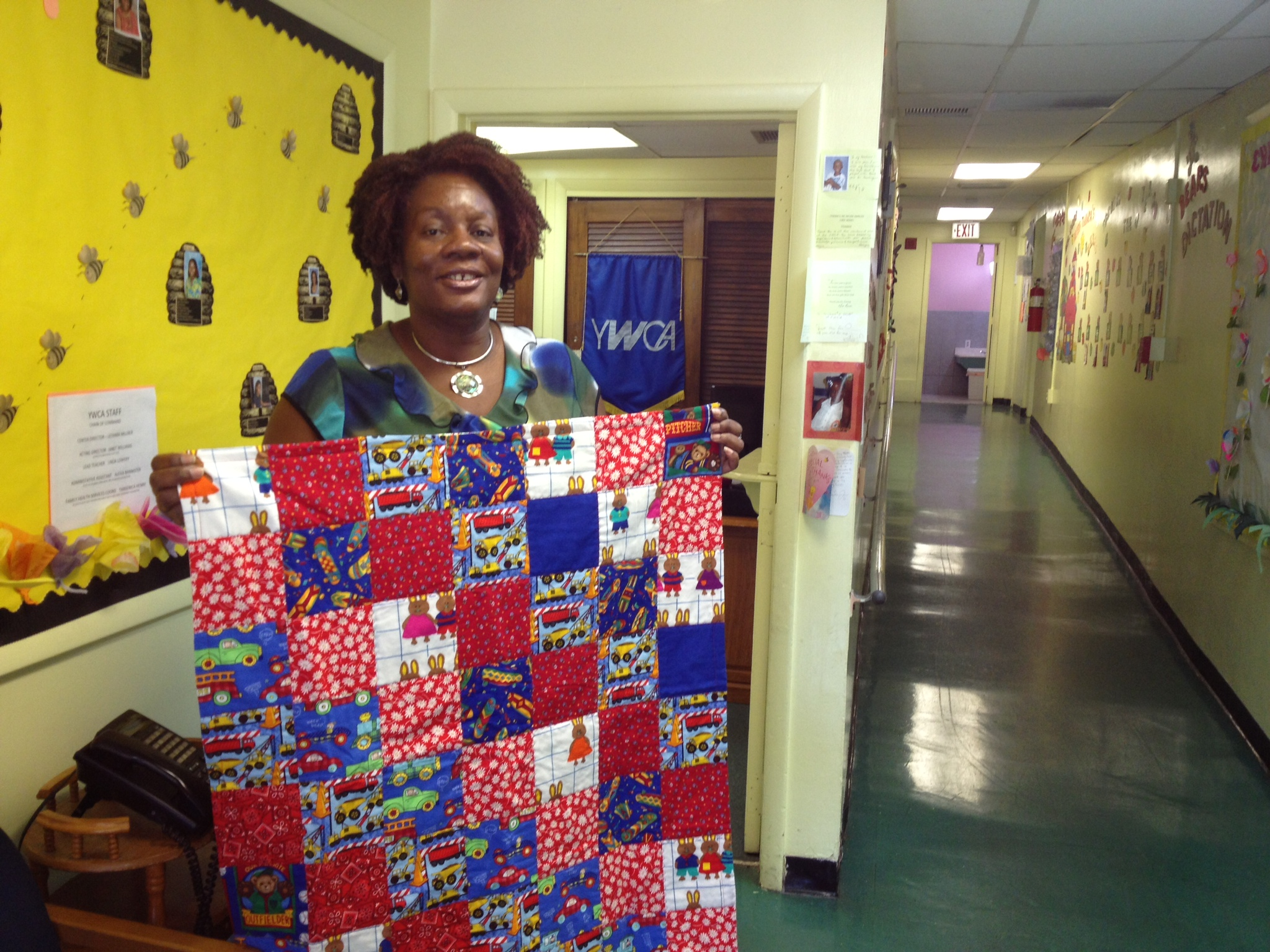 Lethera Millner, Director of the YWCA Child Development Center in West Palm Beach, with quilt donated through Center for Child Counseling.